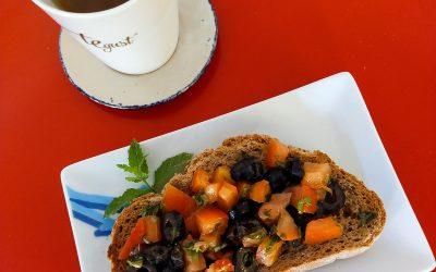 Tomata, ceba, olives negres, alfàbrega i coriandre sobre pa d'espelta integral amb infusió de ratafia fresca-esmorzar